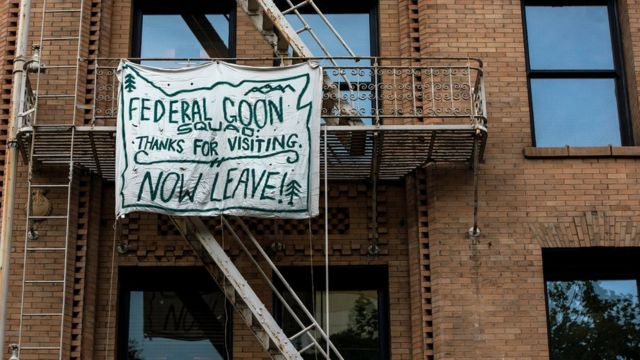 "Banner reading: ""Federal goon squad: Thanks for visiting. Now leave!"""