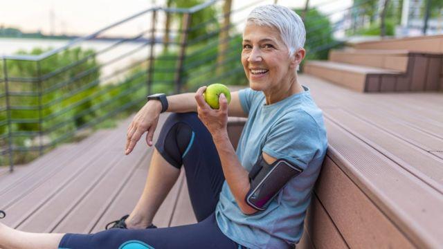 Mulher segura maçã com roupa de exercícios