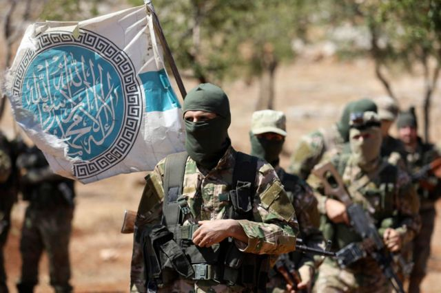 Masked HTS fighters carrying flag