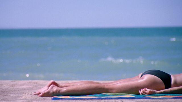 Mujer tomando el sol en una playa