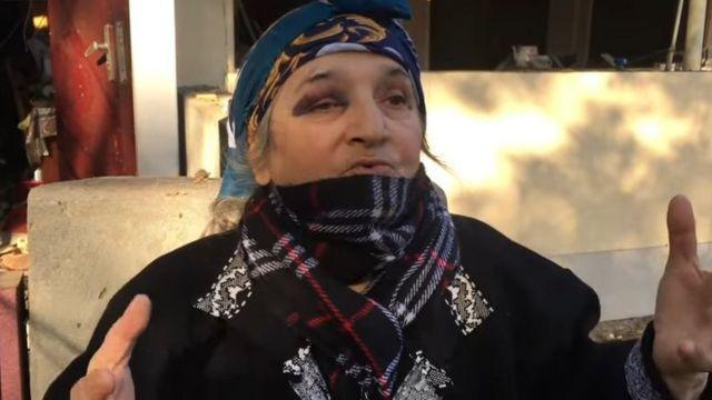 Пожилая жнщина в шарфе и косынке.