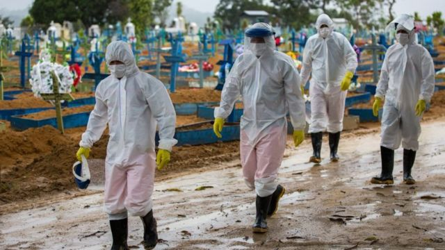 Trabalhadores vestindo roupas de proteção passam pelos túmulos das vítimas do COVID-19 no cemitério Nossa Senhora Aparecida, em Manaus, Brasil, em 25 de fevereiro de 2021