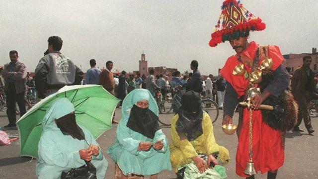 رجل يقدم مشروب لنساء مشاركات في المسيرة الخضراء