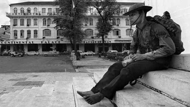 a soldier of the National Liberation Forces (NLF) of North Vietnam surveying the National Assembly building in Saigon