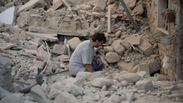 Hombre llora frente a los escombros.