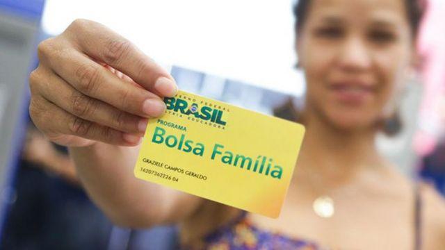 Mulher mostra cartão do programa Bolsa Família