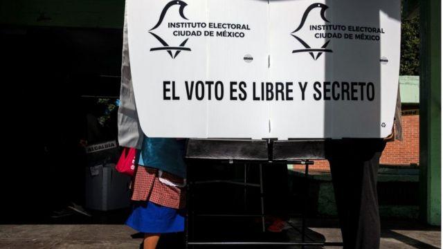 Persona en la urna de votación.