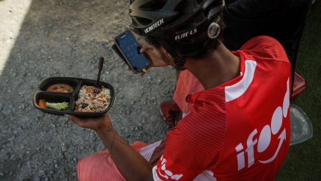 Entregador da Ifood comendo marmita e mexendo no celular