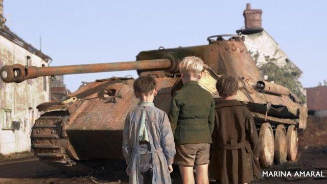 Niños frente a un tanque alemán en la derrota nazi en Francia