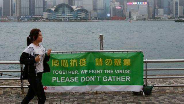 香港九龍尖沙咀一位正在跑步女士經過一面「同心抗疫請勿聚集」橫幅(2/4/2020)