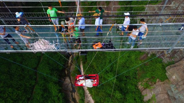 The couple suspended off Shiniuzhai glass bridge, watched by passersby and people organising their suspension, 9 August 2016