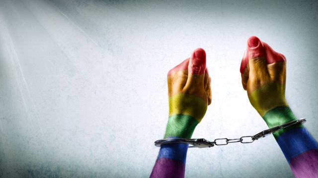 Un par de manos esposadas pintadas con los colores de la bandera gay