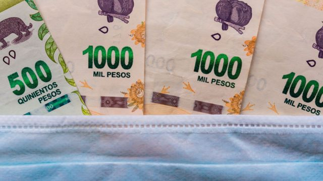 Billetes de pesos debajo de una mascarilla