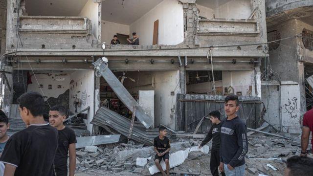 Palestinos inspecionam danos a prédios na rua Al-Saftawi, no norte da Cidade de Gaza