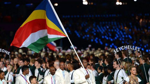 Seychelles Olympic team wey carry di kontri flag.