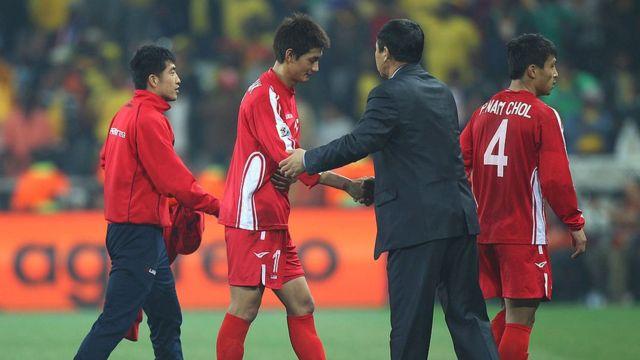 O treinador Kim Jong-Hun cumprimenta jogadores após derrota na Copa do Mundo