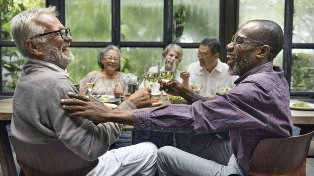 Grupo de personas mayores comiendo y riendo