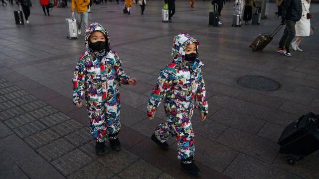 Gêmeos usam máscaras em mercado de rua em Pequim