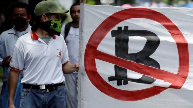 Un hombre con una bandera rechazando el Bitcoin.
