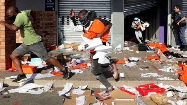 Yağmacılar, Durban, Güney Afrika'daki protesto sırasında Springfield Değer Merkezi'ndeki bir mağazayı boşalttı, 12 Temmuz 2021
