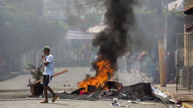 Hombre caminando cerca de una barricada en llamas.
