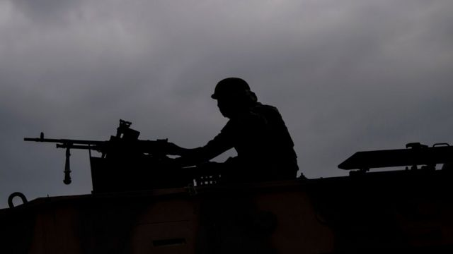 Sombra de um soldado em cima de veículo militar
