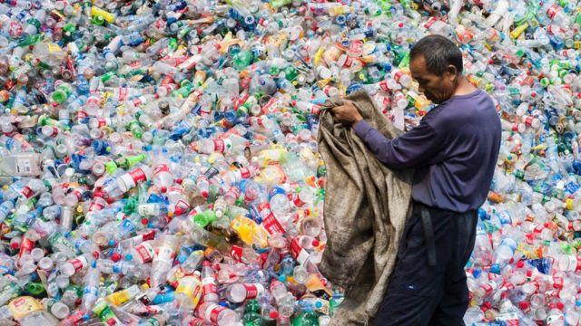 Китайский рабочий рабирает бутылки