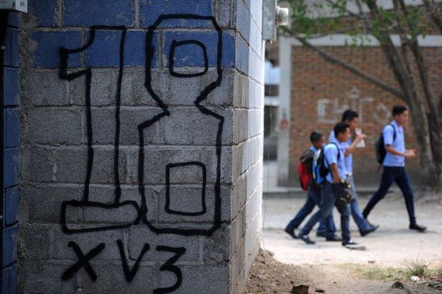 Pintada del Barrio 18 en una pared y al fondo escolares.