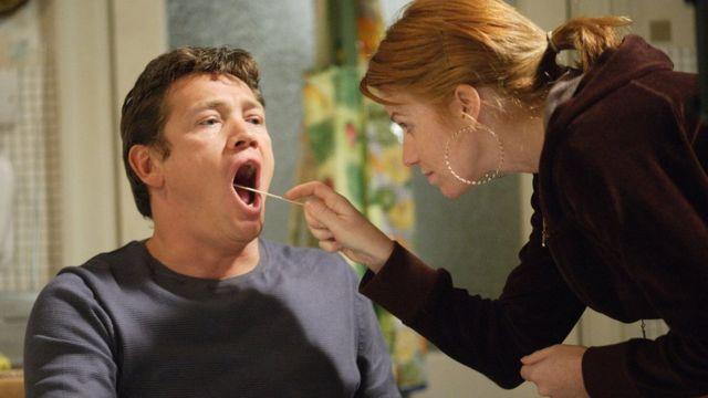 Una mujer toma una muestra de mucosa de la boca de un hombre