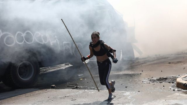 Una manifestante huye de los gases lacrimógenos en las protestas en Chile