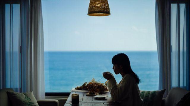 Mulher tomando café sozinha em mesa, em frente ao mar