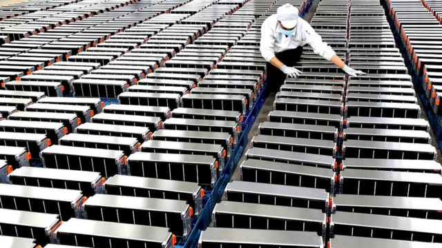 A worker with car batteries at a factory for Xinwangda Electric Vehicle Battery Co. Ltd, which makes lithium batteries for electric cars