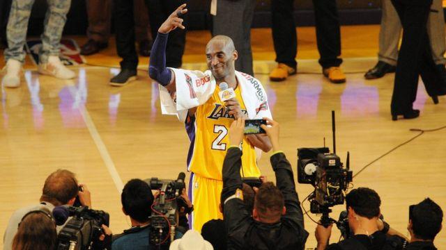 Umukinnyi wa Los Angeles Lakers Kobe Bryant (24) avugana n'abafana nyuma y'umukino warangiye ku manota 101-96 ikipe ye itsinze Utah Jazz kuri sitade ya Staples Center