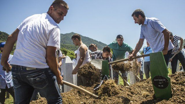 Family members and volunteers bury one of the 136 coffins of newly-identified victims of the 1995 Srebrenica massacre into its final grave mass funeral during the 20th anniversary of the massacre at the Potocari cemetery and memorial on July 11, 2015 in Srebrenica