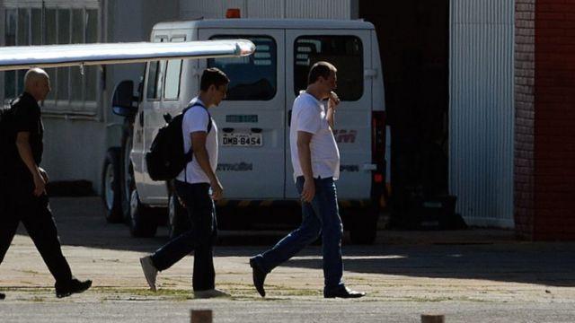 Joesley Batista deixando um avião usando camiseta branca e calça jeans, acompanhado de policiais