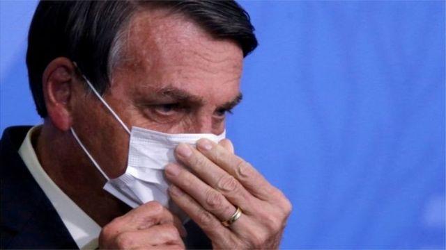 Bolsonaro usa máscara e mexe no rosto