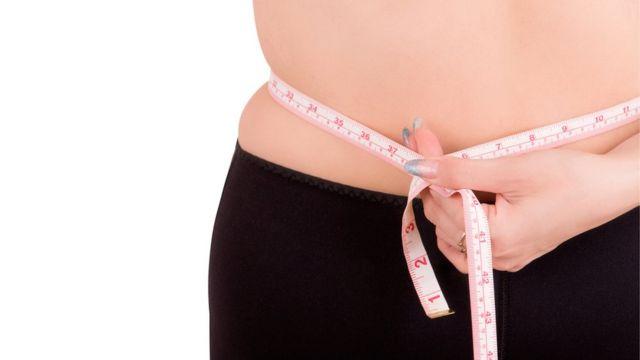 Mujer se mide el abdomen con un centímetro.