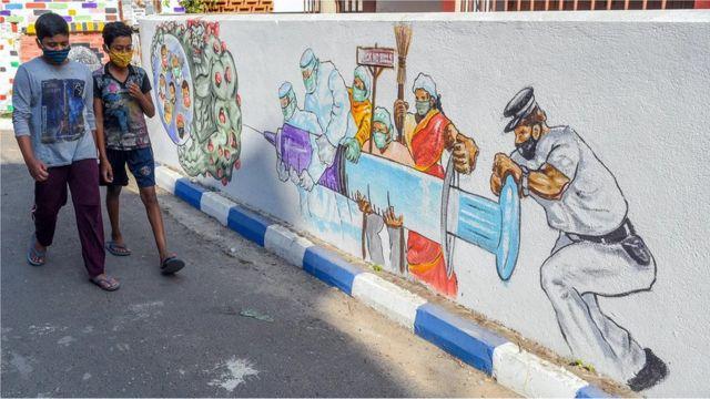 Dos niños caminan junto a un mural de vacunación