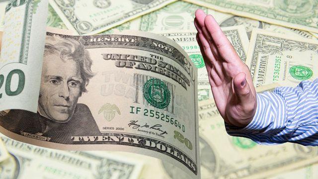 Mão recusando nota de 20 dólares