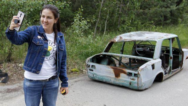 Una turista posa en la zona de exclusión de Chernóbil en la ciudad abandonada de Pripyat