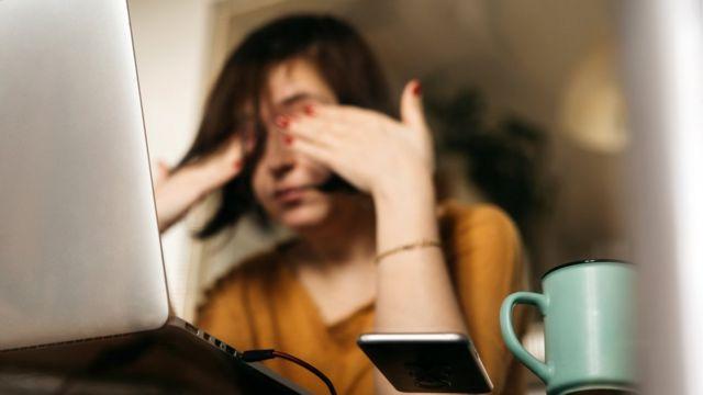 Mulher coçando os olhos na frente do computador