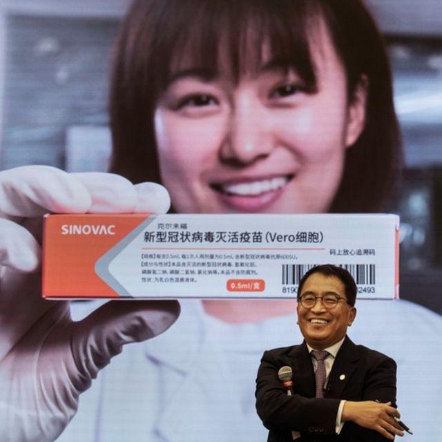 Yin Weidong, presidente de la empresa Sinovac frente a una imagen de la vacuna de su laboratorio