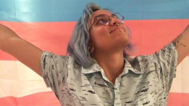 Julian segurando bandeira do orgulho transgênero