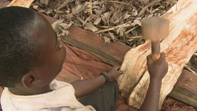 Man hammering bark into cloth
