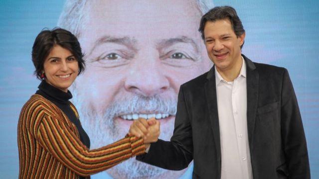 Manuela D'Ávila (esq.) e Fernando Haddad (dir.) em 'debate paralelo' no dia 9 de agosto, em frente a foto de Lula