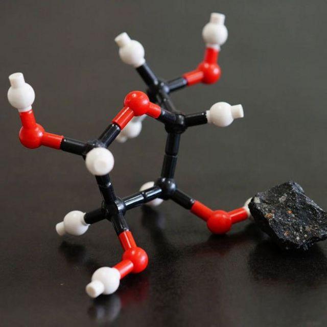Estructura molecular de la ribosa junto a un trozo del meteorito Murchison