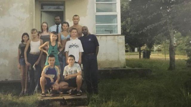 Grupo de niños y adultos frente a un edificio en el complejo de Tarará, Cuba