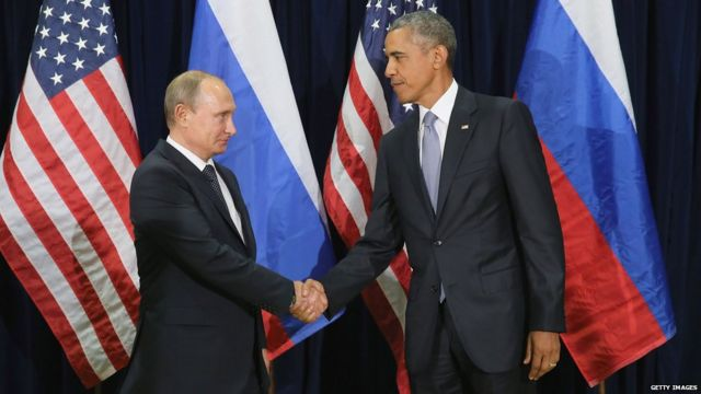 Vladimir Putin shakes hands with Barack Obama