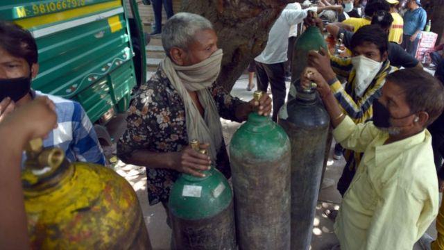 5月1日,在印度新德里,新冠患者的家属在等待给氧气罐补充氧气。