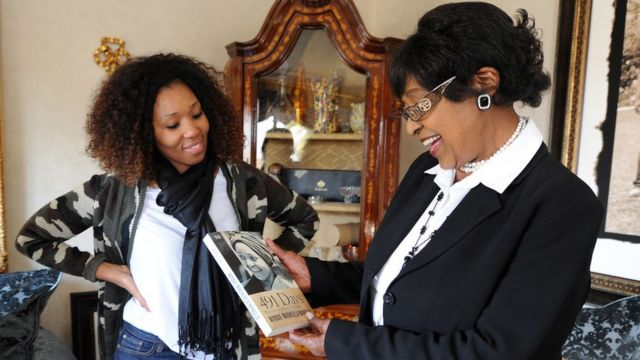 Anti-apartheid campaigner Winnie Madikizela-Mandela (R), ex-wife of former South Africa President Nelson Mandela, receives a first copy of her new book '491 Days: Prisoner Number 1323/69'
